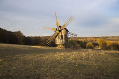 Wooden windmill in a field on a background of autumn forest. Old wooden windmill in the distance in the empty field with yellowed grass on a background of autumn Royalty Free Stock Image