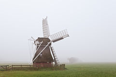 Wooden windmill in fog Stock Photo