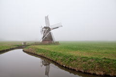 Wooden windmill in fog Stock Photos
