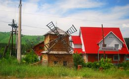 Wooden windmill with red roof. Wooden windmill and a house with red roof on a sunny day with clear bright blue sky Stock Photos
