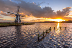 Wooden windmill on lakefront. Tradional wooden windmill on banks of a lake under cloudy sunset in the netherlands Royalty Free Stock Images