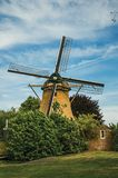 Wooden windmill, leafy bushes and green lawn under sunny blue sky at Weesp. Quiet and pleasant village full of canals and green near Amsterdam. Northern Stock Images