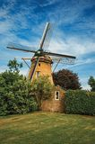 Wooden windmill, leafy bushes and green lawn under sunny blue sky at Weesp. Quiet and pleasant village full of canals and green near Amsterdam. Northern Royalty Free Stock Photography