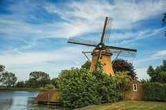 Wooden windmill next to wide river, leafy bushes and green lawn under sunny blue sky at Weesp. Quiet and pleasant village full of canals and green near Royalty Free Stock Photo