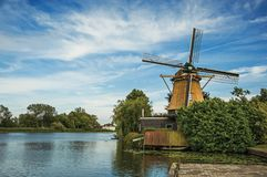 Wooden windmill next to wide river, leafy bushes and green lawn under sunny blue sky at Weesp. Quiet and pleasant village full of canals and green near Stock Image