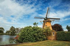 Wooden windmill next to wide river, leafy bushes and green lawn under sunny blue sky at Weesp. Quiet and pleasant village full of canals and green near Stock Photo