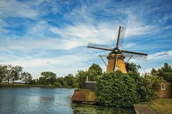 Wooden windmill next to wide river, leafy bushes and green lawn under sunny blue sky at Weesp. Quiet and pleasant village full of canals and green near Stock Photography