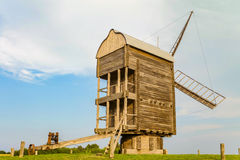 Wooden windmill with steel wheel on the end of the turned up of the rotating mechanism Royalty Free Stock Photo