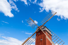 Wooden windmill under blue sky. Old wooden windmill under blue sky. Gotland, Sweden Stock Photos