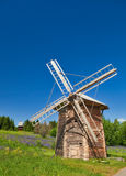 Wooden windmill under clear sky. In the flowered green field Royalty Free Stock Photography