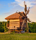 Wooden windmill in the woods at sunset stock image