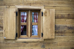 Wooden window. Detail of a wooden window with vintage curtain on wooden house Stock Photography