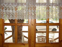 Wooden window. A wooden window with an retro white decorative curtain Stock Image