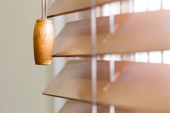 Wooden window blinds partially closed with bright light. Going through. Close up detailed crop, side angle perspective, shallow depth of field Royalty Free Stock Photography