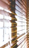 Wooden window blinds partially closed with bright light. Going through. Close up detailed crop, side angle perspective, shallow depth of field Royalty Free Stock Image