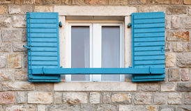 Wooden window with blue open jalousies Royalty Free Stock Images