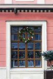 Wooden window with Christmas wreath. And tub with spruce. Festive window royalty free stock images