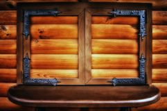 Wooden window with closed shutters and forging elements royalty free stock image