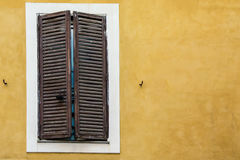 Wooden window with closed shutters and white broad frame on an old wall Royalty Free Stock Image