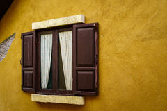 Wooden window with curtain on cracked yellow wall Royalty Free Stock Image