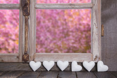 Wooden window with garden view and white hearts Royalty Free Stock Images