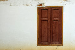 Wooden window on old white wall. Royalty Free Stock Photo