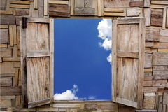 Wooden window opening over view of blue sky and cloud Stock Image