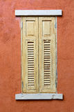 Wooden window on orange grunge wall Stock Photography