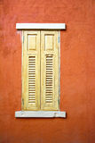 Wooden window on orange wall background. Royalty Free Stock Photo