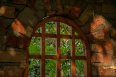 Wooden window of a red brick bungalow in the garden royalty free stock photography