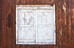 Wooden window in rusted metal surface Royalty Free Stock Photography