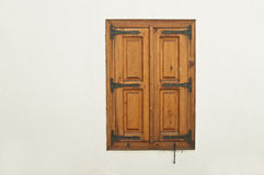 Wooden window shutter with metal decoration on white wall Stock Images