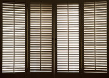 Wooden Window Shutters. Wooden shutters in front of bright, sunlit windows Royalty Free Stock Image
