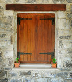 Wooden window in the stone wall Stock Image