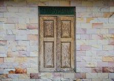 Wooden window on stone wall Stock Photo