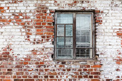 Wooden window on weathered red brick wall painted white Royalty Free Stock Photo