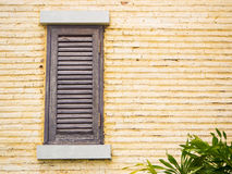Wooden window on yellow brick wall Royalty Free Stock Photography