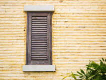 Wooden window on yellow brick wall Stock Photos