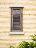 Wooden window on yellow brick wall Royalty Free Stock Photo