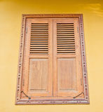 Wooden window on yellow cement wall Royalty Free Stock Image
