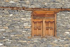 Wooden windows in an old stone wall in the village of Manang, Himalayas, Nepal Royalty Free Stock Photo