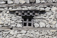 Wooden windows in an old stone wall in the village of Manang, Himalayas, Nepal . Royalty Free Stock Photos