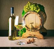 Wooden wine barrel and bunch of ripe grape. White wine. Wooden wine barrel and bunch of ripe grape. Bottle of white wine, wine glass, corkscrew and corks on stock photo