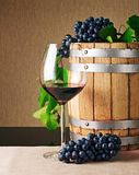 Wooden wine barrel and glass of red wine on table royalty free stock image