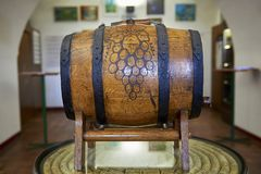 Wooden wine barrel with grape pattern in the middle lying on wooden stand on a table. Znojmo, Czech Republic - July 4, 2018: Monastery Loucky klaster. Znovín stock images