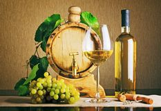 Wooden wine barrel with grape twig. Bottle of white wine. Wine glass, corkscrew, corks and bunch of ripe grape on table. Eco winemaking product. Classical stock images