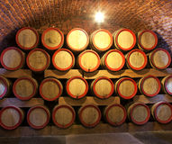 Wooden wine barrels are stored in winery cellar Stock Photos