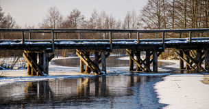 Wooden winter bridge over the river Royalty Free Stock Images