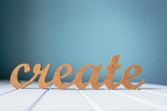 Wooden word create against a blue background Stock Photos