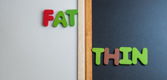 Wooden word FAT and THIN on black board and white board. 1 Stock Photo